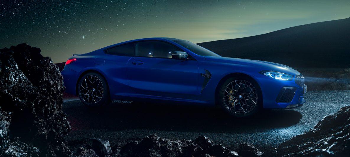 BMW M8 Competition Coupé in Marina Bay Blau metallic, stehende Dreiviertel-Seitenansicht bei Nacht.